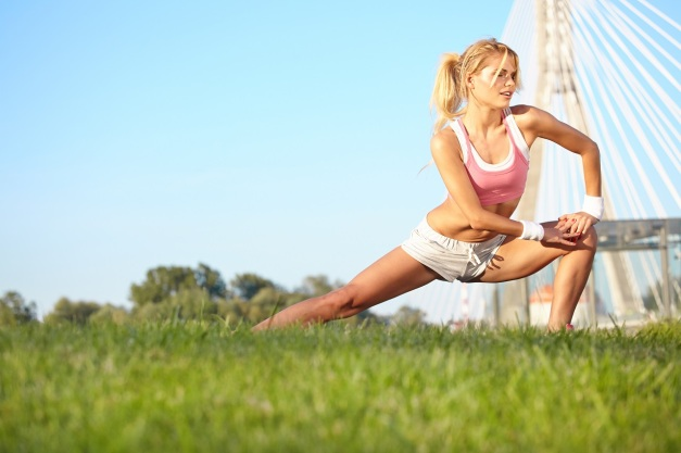 woman stretching hamstring leg muscles during outdoor running workout.